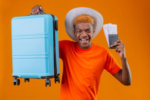 Heureux Jeune Beau Garçon Portant Un T-shirt Orange Tenant Une Valise De Voyage Et Des Billets D'avion Photo gratuit