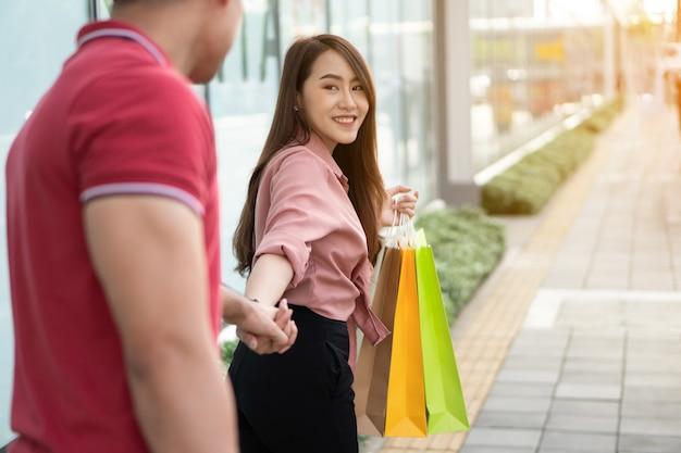 Heureux jeune couple d'acheteurs marchant dans la rue commerçante vers black friday shopping Photo Premium