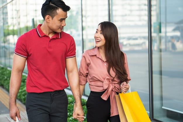 Heureux jeune couple d'acheteurs marchant dans la rue commerçante vers et tenant des sacs colorés Photo Premium