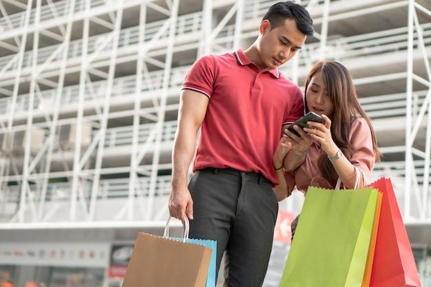 Heureux Jeune Couple D'acheteurs Marchant Dans La Rue Commerçante Vers Photo Premium