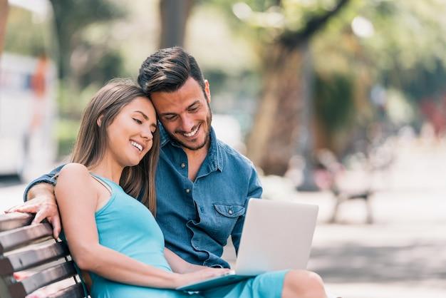 Heureux jeune couple à l'aide d'un ordinateur portable assis sur un banc dans la ville en plein air Photo Premium