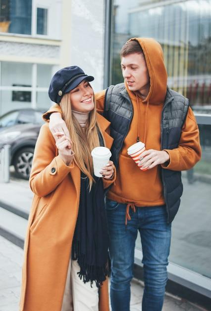 Heureux jeune couple amoureux amis adolescents habillés dans un style décontracté marcher ensemble sur la rue de la ville en saison froide Photo Premium
