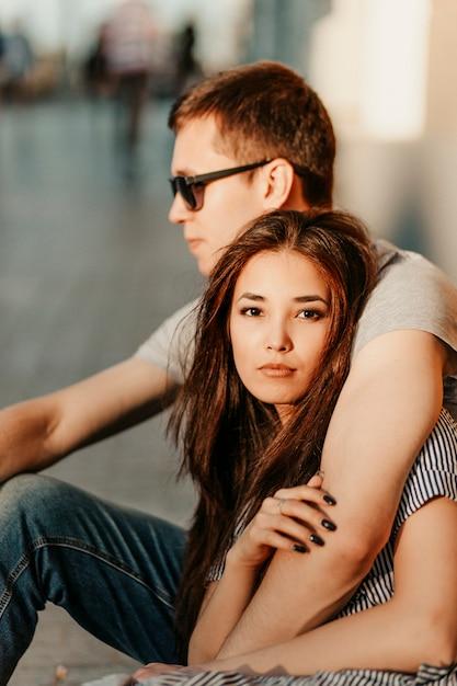 Heureux jeune couple amoureux amis d'adolescents habillés en style décontracté assis ensemble Photo Premium