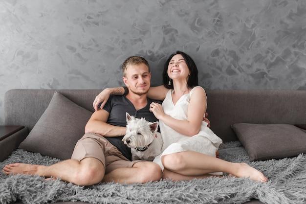 Heureux jeune couple assis sur le canapé avec un chien blanc Photo gratuit