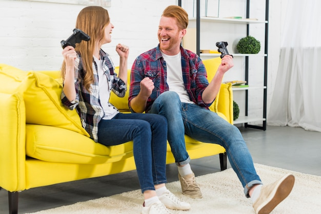 Heureux jeune couple assis sur un canapé jaune serrant le poing comme vainqueur après avoir joué au jeu vidéo Photo gratuit