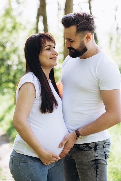 Heureux jeune couple attend bébé dans le parc de l'été Photo Premium