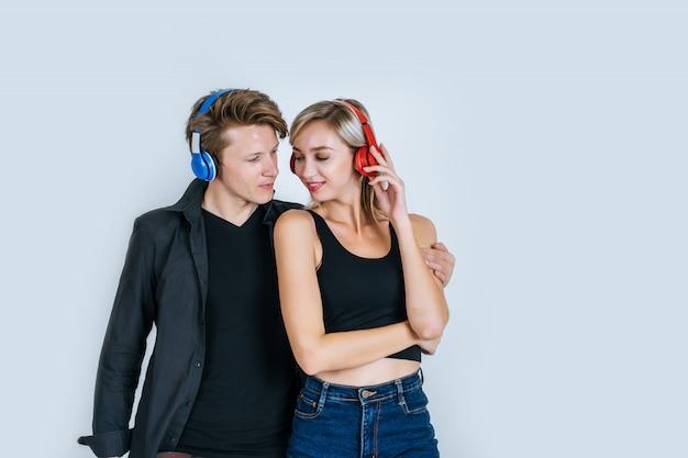 Heureux jeune couple au casque d'écoute de musique Photo gratuit