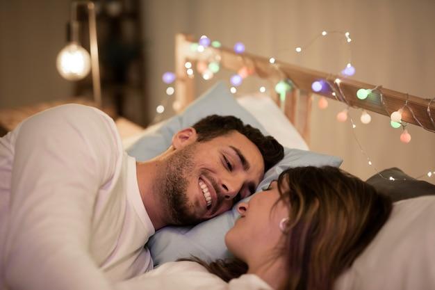 Heureux jeune couple câlins au lit Photo gratuit