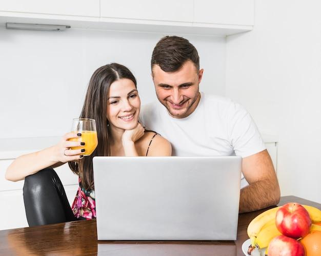Heureux Jeune Couple Cherche Un Ordinateur Portable Dans La Cuisine Photo gratuit