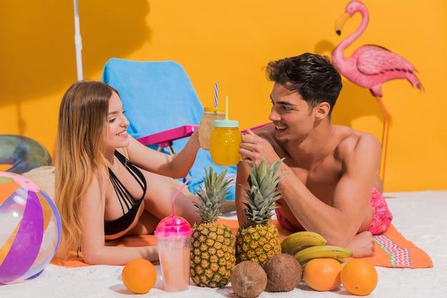 Heureux jeune couple couché avec des cocktails sur la plage en studio Photo gratuit
