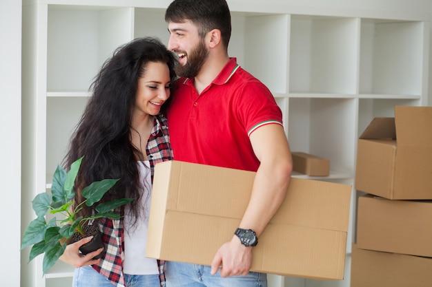 Heureux jeune couple déballant et emménageant dans une nouvelle maison Photo Premium