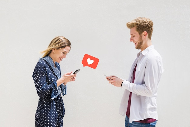 Heureux jeune couple échangeant des messages d'amour Photo gratuit