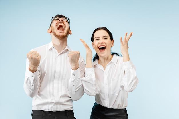 Heureux Jeune Couple Excité Avec Délice. Homme Affaires, Et, Femme, Isolé, Sur, Mur Bleu Photo gratuit