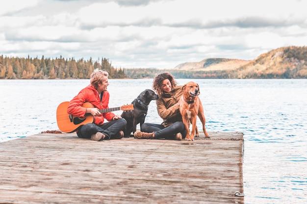 Heureux jeune couple jouant avec un chien sur un quai Photo Premium