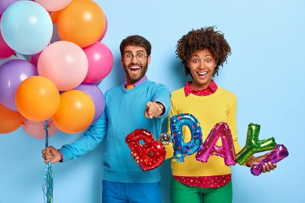 Heureux Jeune Couple Lors D'une Fête Posant Avec Des Ballons Photo gratuit