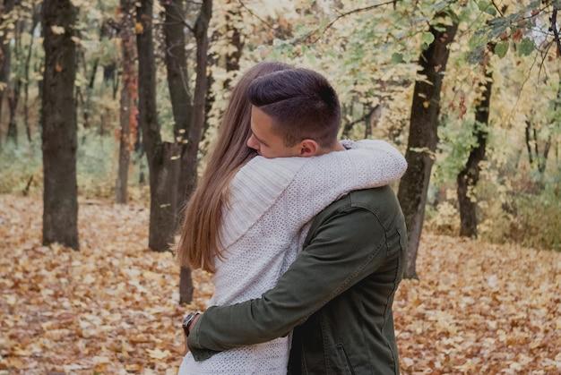 Heureux jeune couple marchant un jour d'automne dans le parc. Photo Premium