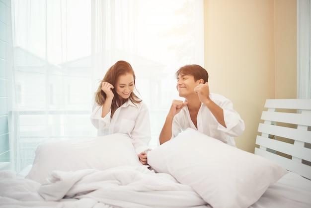 Heureux jeune couple s'amuse au lit Photo gratuit