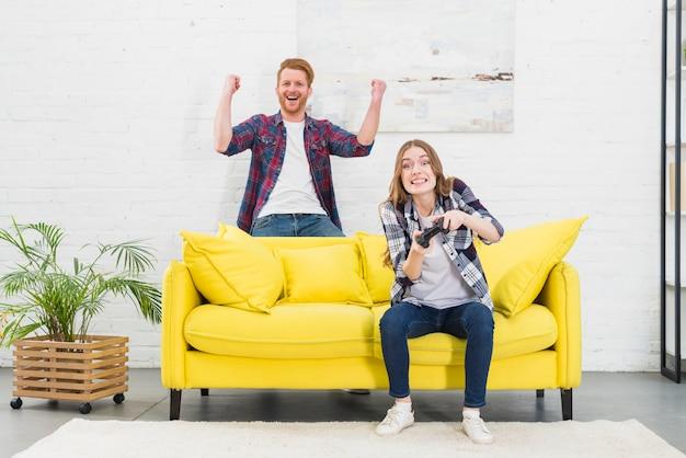 Heureux jeune couple s'amuse à jouer à un jeu vidéo à la maison Photo gratuit