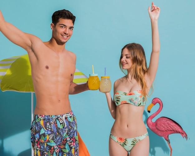 Heureux jeune couple s'amuser avec des cocktails en studio Photo gratuit