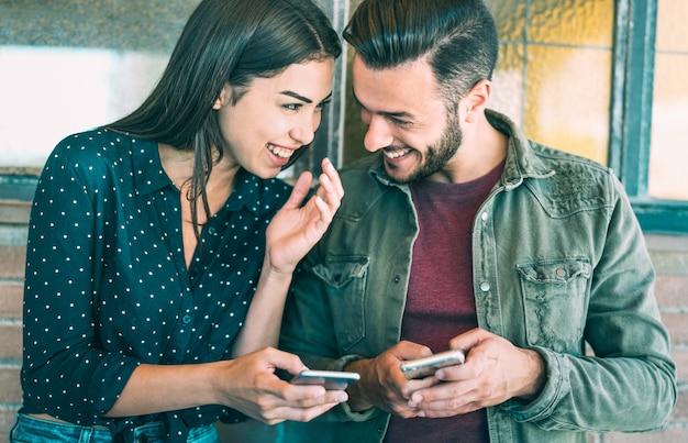 Heureux jeune couple s'amuser avec un téléphone mobile intelligent à la place urbaine Photo Premium