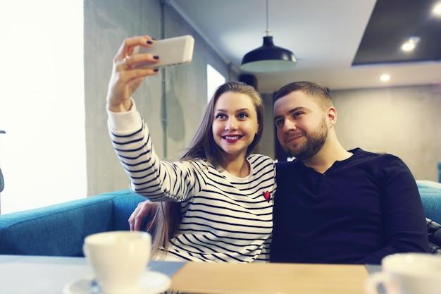 Heureux jeune couple avec smartphone prenant selfie au café en centre commercial Photo Premium