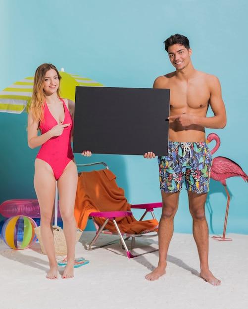 Heureux jeune couple tenant un panneau noir sur la plage Photo gratuit