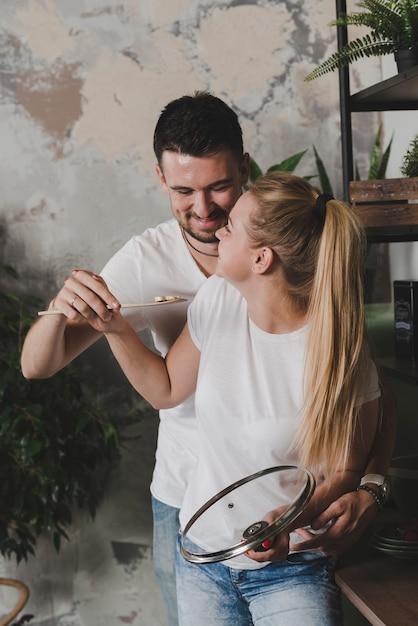 Heureux jeune couple tenant une tranche de champignons sur une spatule Photo gratuit