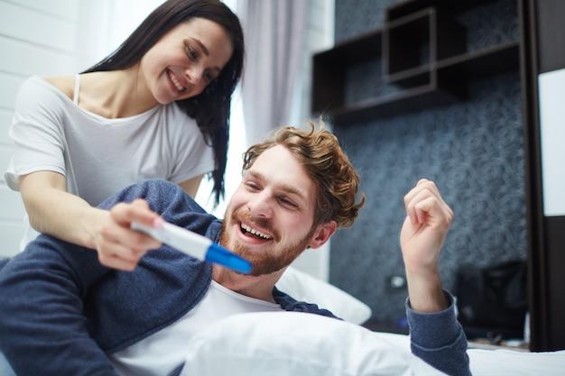 Heureux jeune couple avec test de grossesse Photo gratuit