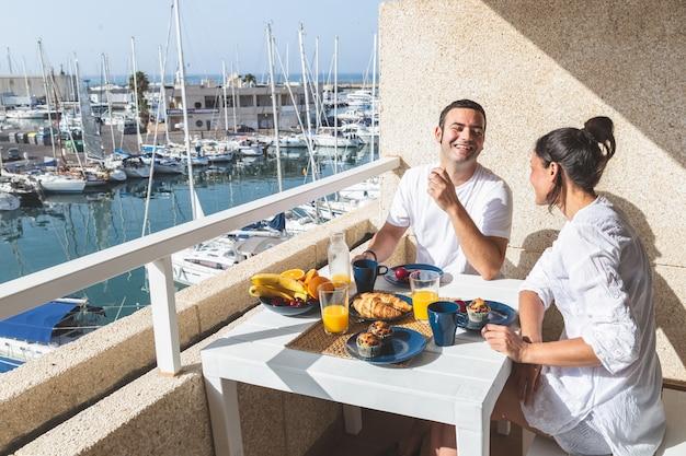 Heureux jeune couple en train de prendre son petit déjeuner sur la terrasse Photo Premium
