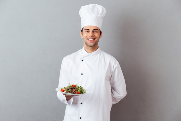 Heureux Jeune Cuisinier En Uniforme Tenant La Salade. Photo gratuit