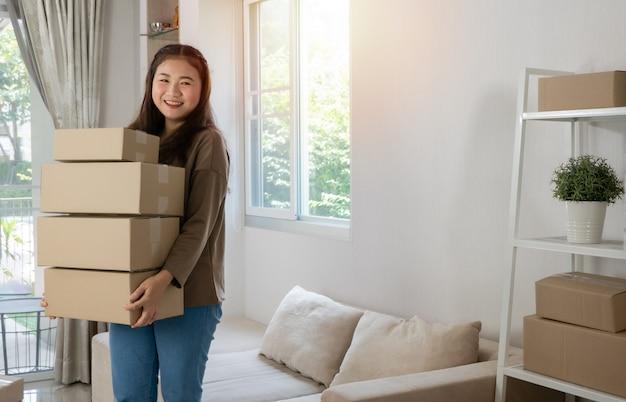 Heureux Jeune Entrepreneur Asiatique Organise Des Boîtes à Livrer Aux Clients Photo Premium