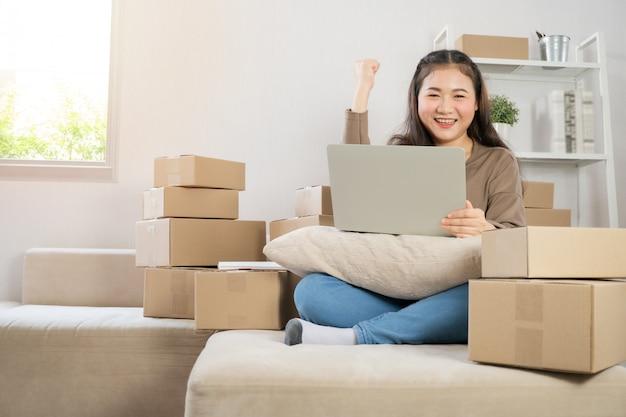 Heureux Jeune Entrepreneur Asiatique, Sourire Pour Le Succès Des Ventes Après Avoir Vérifié La Commande De La Boutique En Ligne Photo Premium