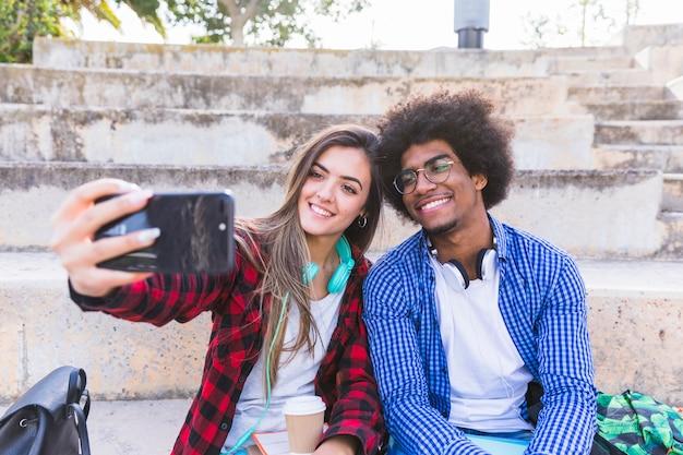 Heureux jeune étudiant et femme prenant selfie sur téléphone mobile à l'extérieur Photo gratuit