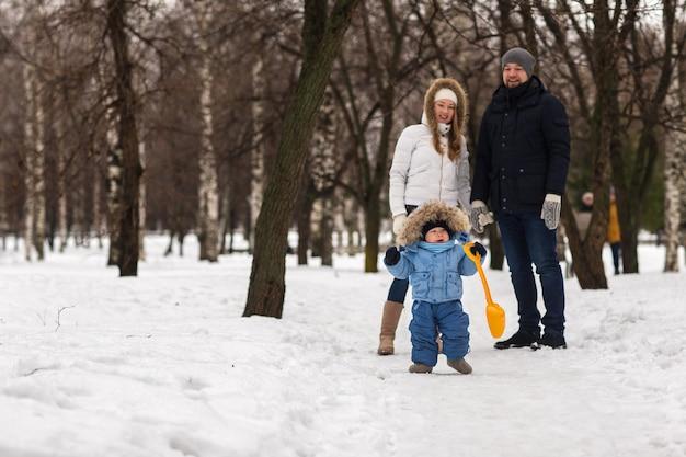 Heureux jeune famille marchant dans un parc d'hiver Photo Premium