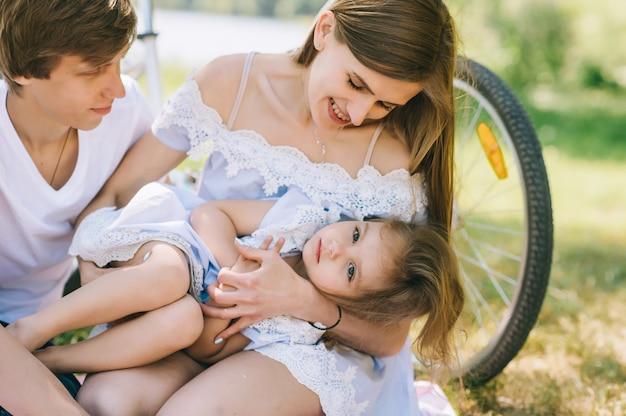 Heureux jeune famille passer du temps ensemble à l'extérieur. père mère et leur enfant dans le parc verdoyant Photo Premium