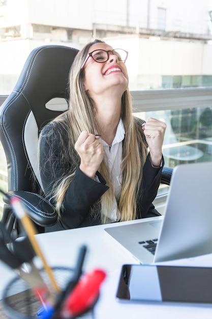 Heureux jeune femme d'affaires assis sur le lieu de travail Photo gratuit