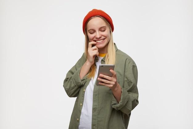 Heureux Jeune Femme Blonde Aux Cheveux Longs Avec Maquillage Naturel Tenant Le Téléphone Mobile Dans La Main Levée Et Souriant Tout En Vérifiant Les Réseaux Sociaux, Isolé Sur Bleu Photo gratuit