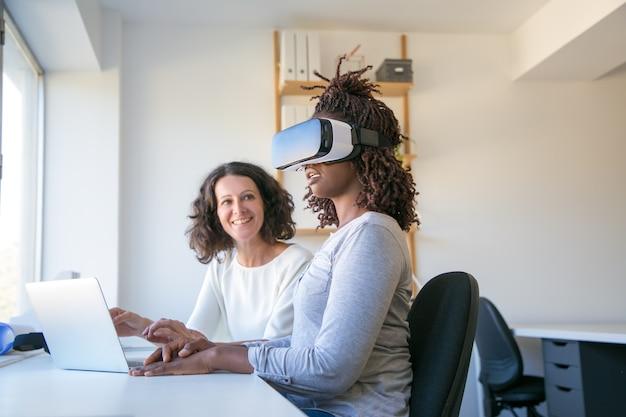 Heureux jeune femme dans le casque de réalité virtuelle Photo gratuit