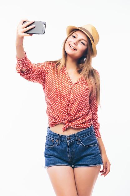Heureux Jeune Femme Flirter à Prendre Des Photos D'elle-même Par Téléphone Portable, Sur Fond Blanc Photo gratuit