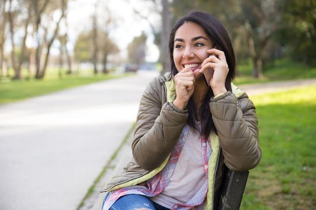 Heureux jeune femme rire tout en parlant au téléphone Photo gratuit