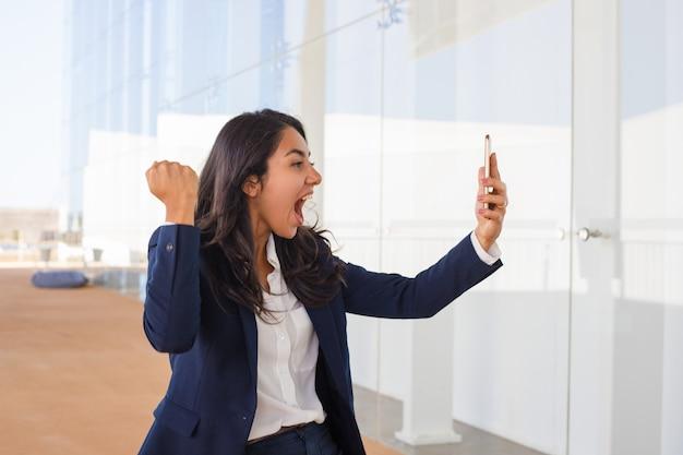 Heureux jeune femme tenant un smartphone Photo gratuit