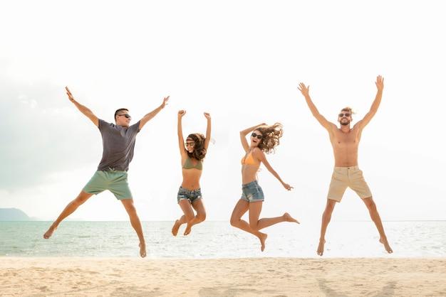 Heureux jeune groupe énergique d'amis sautant sur la plage en été Photo Premium
