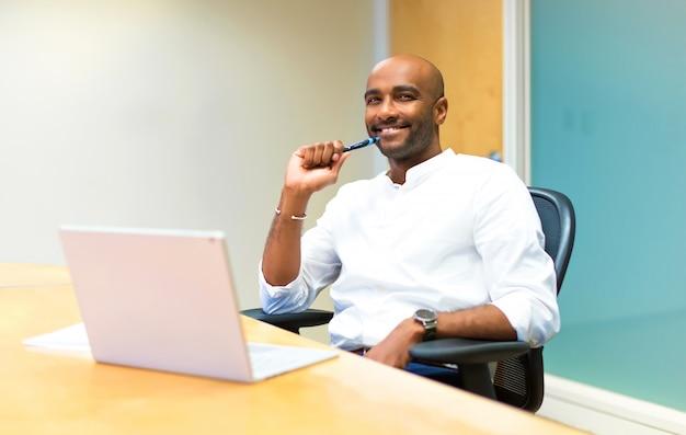 Heureux jeune homme d'affaires américain afro au bureau avec son ordinateur portable Photo Premium