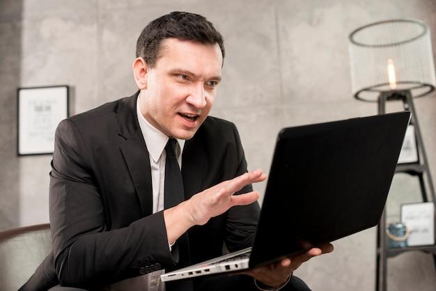 Heureux jeune homme d'affaires expliquant et faisant des gestes Photo gratuit