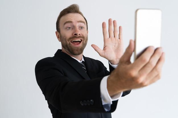 Heureux jeune homme d'affaires parlant via un lien vidéo Photo gratuit