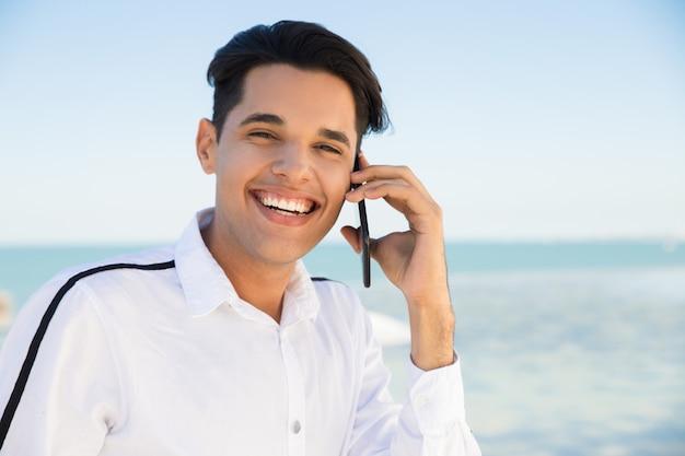 Heureux jeune homme appelant à l'extérieur du smartphone Photo gratuit