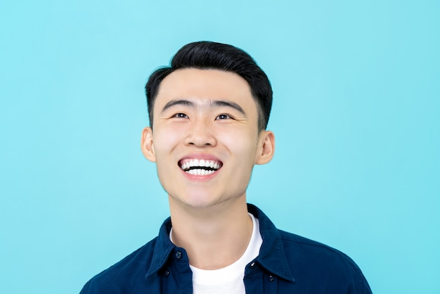 Heureux Jeune Homme Asiatique Souriant Et Regardant Vers Le Haut Photo Premium