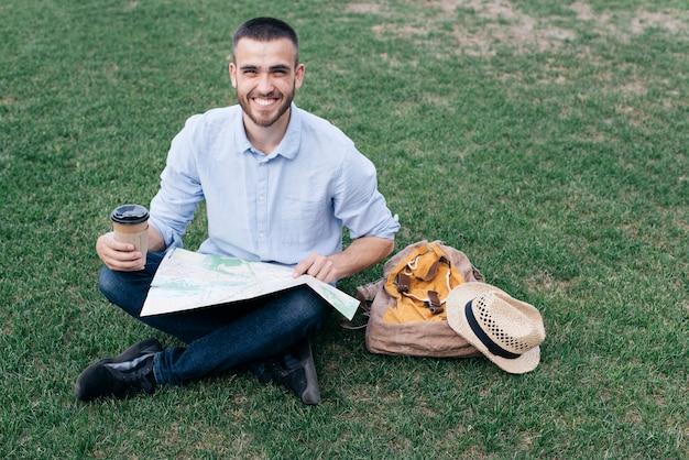 Heureux jeune homme assis sur l'herbe avec une tasse de café jetable et carte Photo gratuit