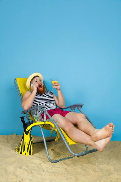 Heureux Jeune Homme Au Repos, Prend Selfie, Boire Des Cocktails Sur L'espace Bleu Photo gratuit