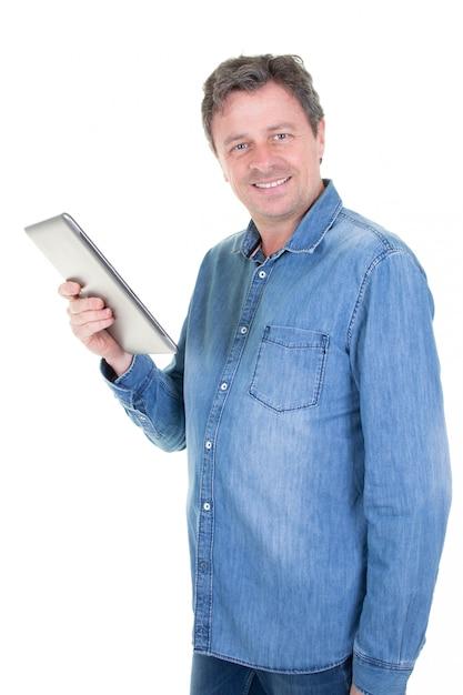 Heureux jeune homme en chemise de jeans bleu debout et à l'aide de tablette sur blanc Photo Premium
